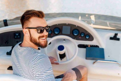 Happy yacht owner. Smiling young man holding hand on steering wheel while driving yacht